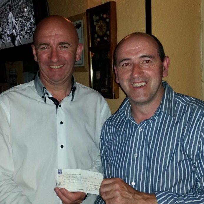 Mick Saunders being presented his 50/50 winnings by Peter Browne