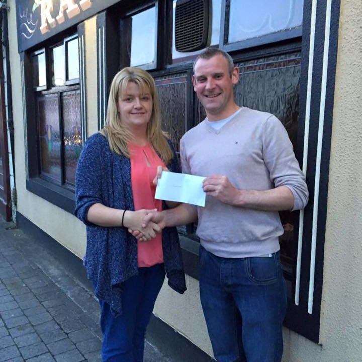 David Grant receiving his 50/50 cheque from Louise Murphy